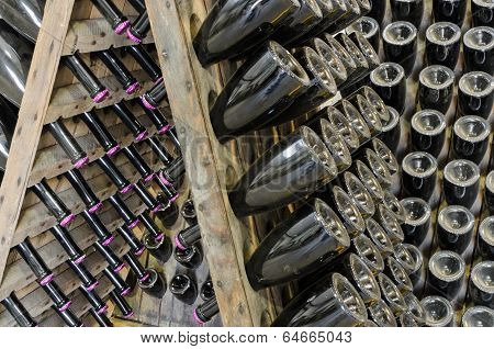 Dusty Bottles With Brut Sparkling Wine On Wooden Rack