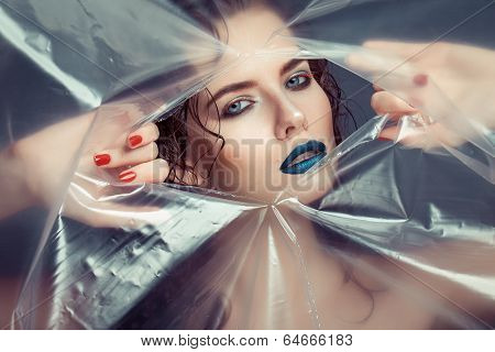 Woman With Creative Eye Makeup Peering Cellophane