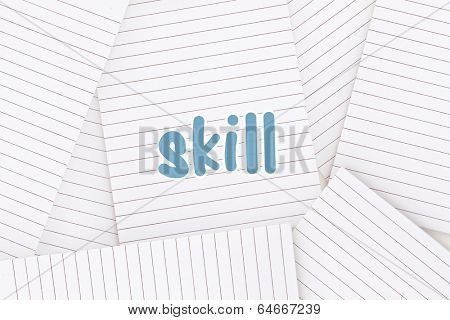 The word skill against lined paper strewn over surface