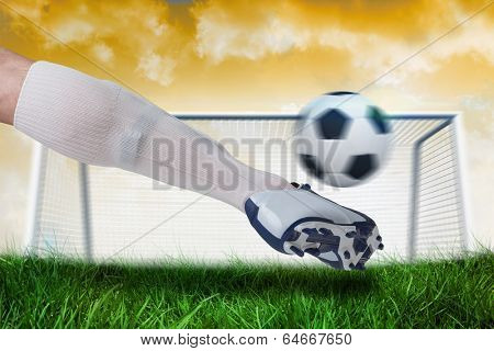 Composite image of close up of football player kicking ball against goalpost on grass under yellow sky