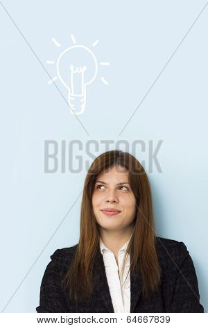 Beautiful business woman smiling and thinking of a brilliant idea with light bulb above her head