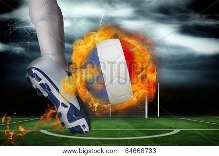 Football player kicking flaming france flag ball against football pitch under stormy sky