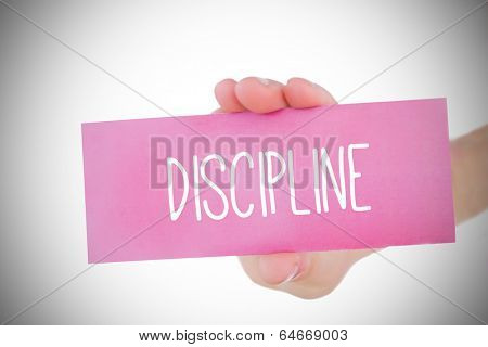 Woman holding pink card saying discipline against white background