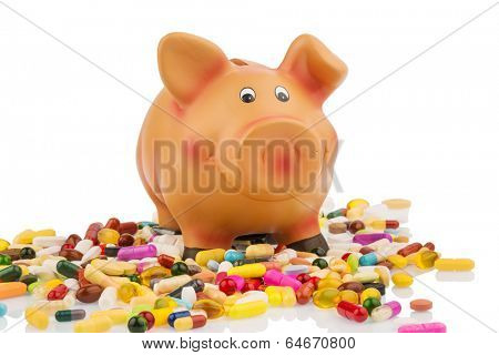 pills lying next to a piggy bank. symbolic photo for costs in medicine and pharmaceutical industry