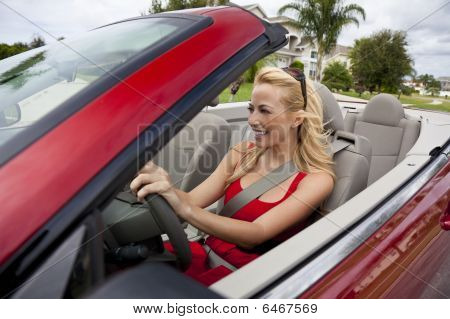 Beautiful Young Woman Driving Convertible Car Wearing Sunglasses
