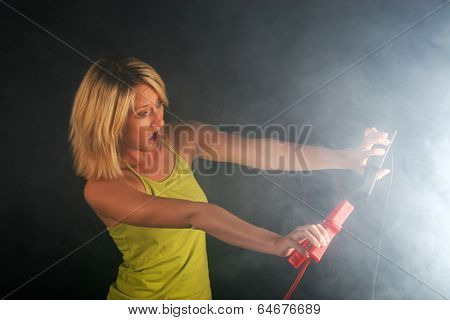 Blonde girl with cables for starting an engine with smoke