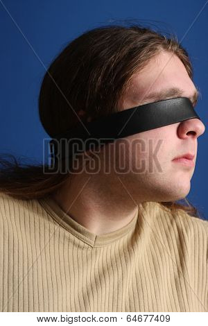 Man with a belt over his eyes