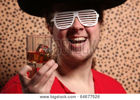 Crazy rock and rollerer with a big black hat, party glasses and a glass of whiskey in front of a cheetah skin background