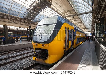 Amsterdam, Netherlands - March 19, 2014: Yellow Train Stands On The Central Railroad Station In Amst