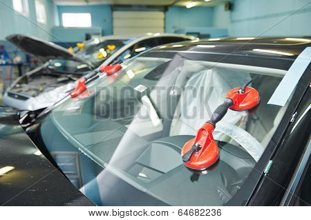 Automobile car windshield or windscreen service concept in auto service station garage