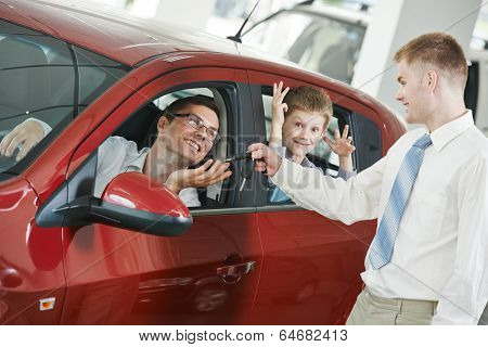 Car salesperson sells new automobile to young family with child