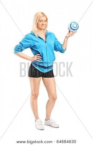 Full length portrait of a female handball player holding a ball isolated on white background