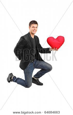 Man crouching on one knee and holding a red heart isolated on white background