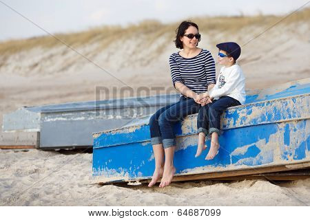 Mother and her little son sitting on a boat