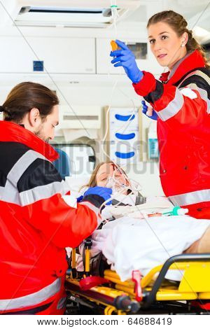 Emergency doctor and nurse or ambulance team medicate accident victim