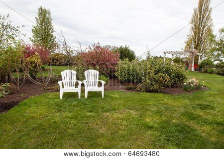 Two Lawn Chairs In A Garden