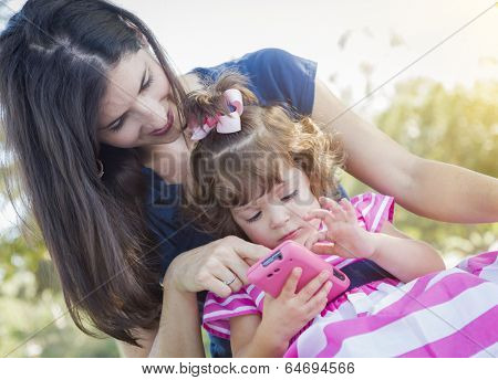 Mixed Race Mother and Cute Baby Daughter Playing with Cell Phone in Park.