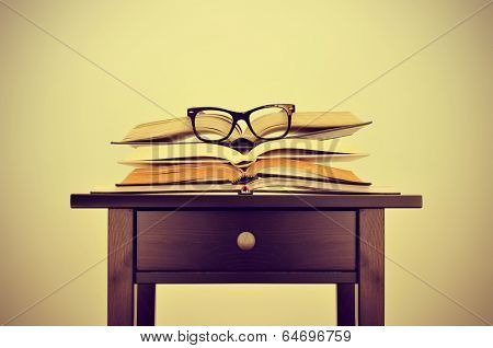 a pile of books and a pair of eyeglasses on a desk, symbolizing the concept of reading habit or studying, with a retro effect