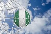 foto of nigeria  - Football in nigeria colours at back of net against bright blue sky with clouds - JPG