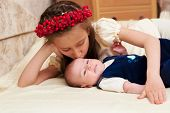 foto of emo-boy  - Older sister hugging baby lying on the bed - JPG
