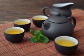 stock photo of teapot  - Green tea in cups with mint and teapot on bamboo mat - JPG