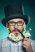 stock photo of peace-pipe  - Extravagant man with a beard of flowers wearing elegant top hat and smoking a pipe - JPG