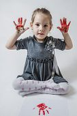 foto of finger-painting  - Llittle cute blonde girl playing and painting with finger paint  - JPG