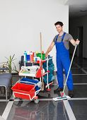 stock photo of sweeper  - Portrait Of Young Happy Man Standing With Cleaning Equipment In Office - JPG