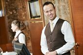 picture of receptionist  - Happy receptionist worker standing at hotel counter - JPG