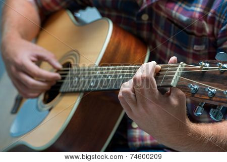 close up of a male musician playing acoustic guitar