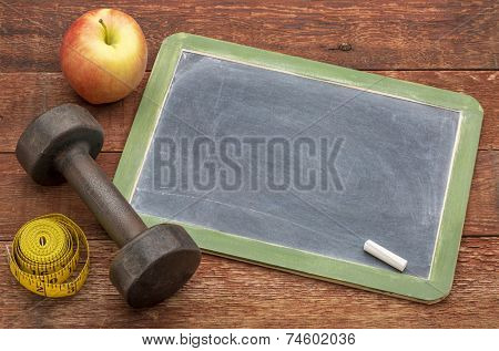 blank slate blackboard sign against weathered red painted barn wood with a dumbbell, apple and tape measure, ready for text related to fitness, diet or weight loss