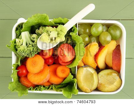 Tasty vegetarian food in plastic box on green wooden table
