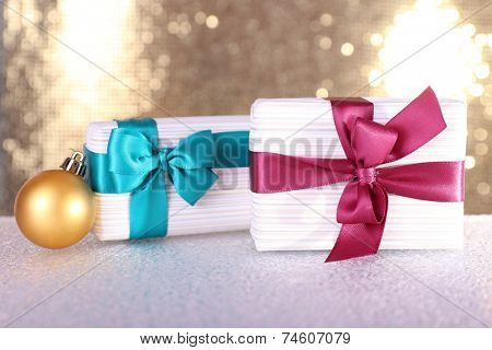 Gift boxes with vinous and blue ribbons and Christmas tree toy on table on shiny background