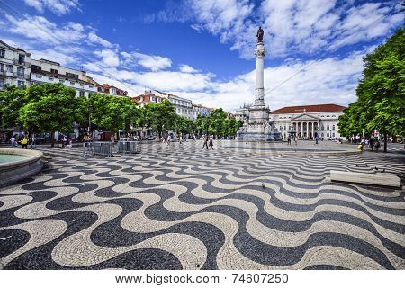 LISBON, PORTUGAL - OCTOBER 13, 2014: Pedestrians stroll through Rossio Square. Officially called Pedro IV Square, it serve as a popular meeting point for tourists and locals alike.