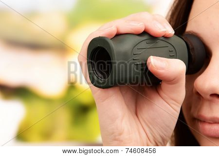 Modern monocular in hands on bright background