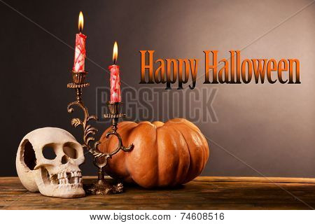 Bloody candles for Halloween holiday and decorative skull, pumpkin, on wooden table, on dark background