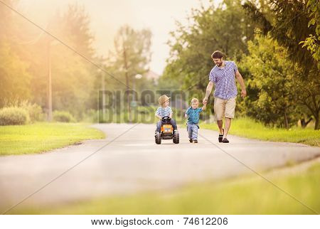 Father with sons have fun on road