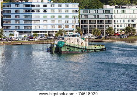 Old Green Tugboat By Modern Buildings