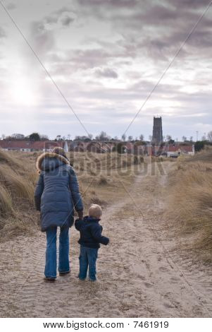 A Woman And Son Walk Down An English Country Path Towards A Village Church