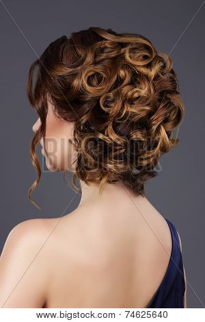 Rear View Of Woman's Festive Hairstyle. Waved Hairs