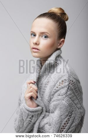 Portrait Of Young Pretty Woman In Knitted Woolen Gray Jersey