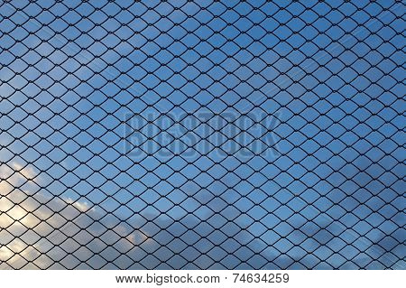 Metal wire mesh and evening blue sky in background