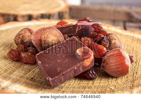 Chocolate Bars With Nuts And Raisins On Wooden Stump