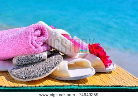 Natural Bath Sponges, Bath Slippers, Pumice And Towel Against Blue Ocean