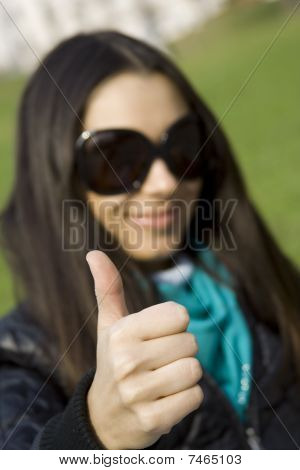 Beautiful girl in a park smiling. Thumb sign OK