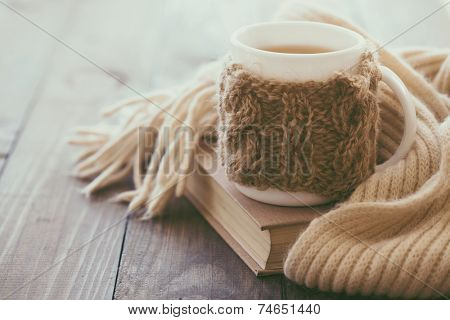 Cup of hot tea with lemon dressed in knitted warm winter scarf on brown wooden tabletop, soft focus