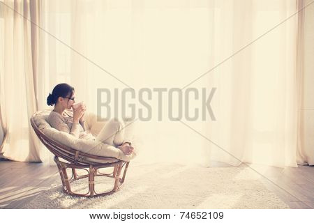 Young woman at home sitting on modern chair in front of window relaxing in her living room reading book and drinking coffee or tea