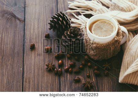 Cup of hot tea with lemon dressed in knitted warm winter scarf on brown wooden tabletop, top view point