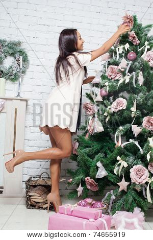 Fashion and sexy african woman decorating christmas tree