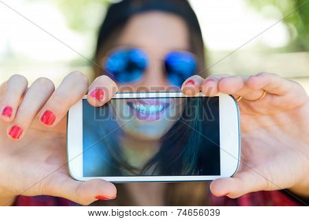 Portrait Of Beautiful Girl Taking A Selfie With Mobile Phone In City.